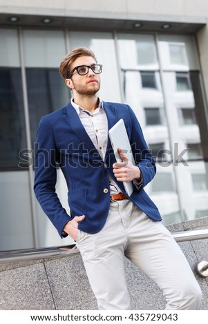 Cheerful man is waiting for someone with laptop - stock photo