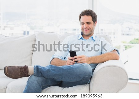 Cheerful man sitting on the couch using his smartphone at home in the living room - stock photo