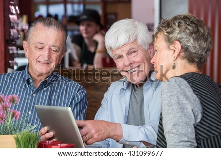 Cheerful man with mature friends on wifi with their tablet computer in a coffee house - stock photo