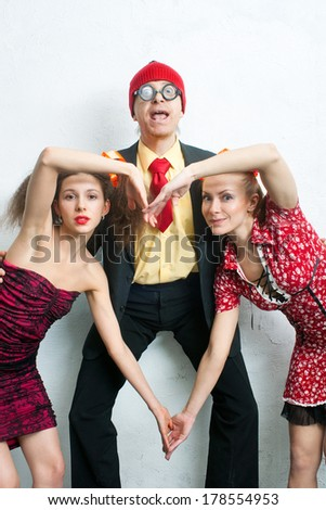 Cheerful man with two charming girlfriends - stock photo