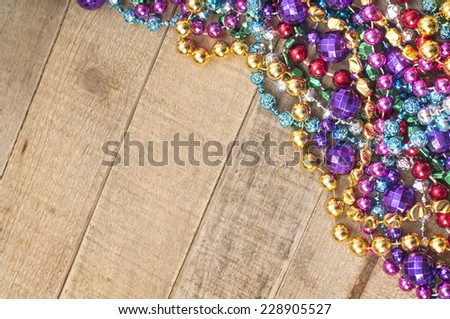 Cheerful Mardi Gras Beads in corner on Rustic Wood Board Background from above with room or space for copy, text, your words.  Horizontal - stock photo
