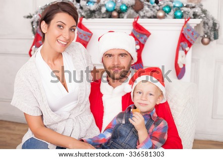 Cheerful married couple and child are celebrating Christmas. The man is wearing costume of Santa Claus and sitting in chair. He is holding woman and boy on knees. They are smiling - stock photo