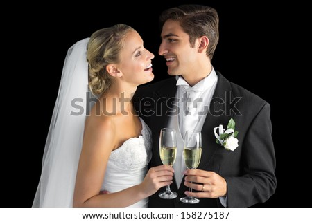 Cheerful married couple holding champagne glasses on black background - stock photo
