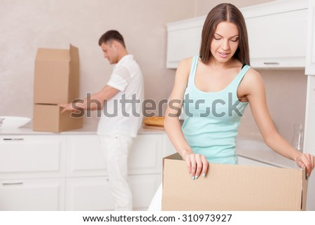 Cheerful married couple is packing staff for move in new house. They are putting things in cardboard boxes with concentration. Focus on women. She is gently smiling - stock photo