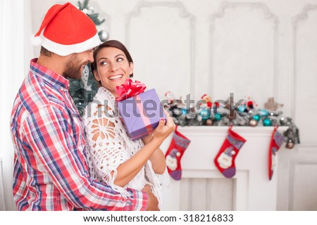 Cheerful married couple is standing near New Year tree. The woman is holding a box of gift and looking at man with joy. They are embracing and smiling. Copy space in right side - stock photo