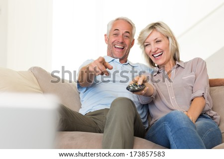 Cheerful mature couple watching tv on sofa at home - stock photo