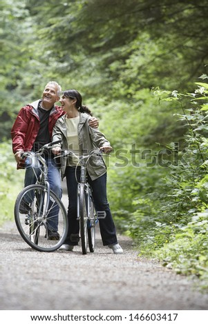 Cheerful mature man and middle aged woman with bikes on forest road - stock photo