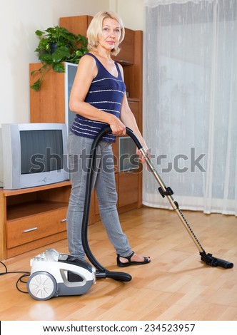 cheerful  mature woman cleaning with vacuum cleaner on parquet floor at home - stock photo