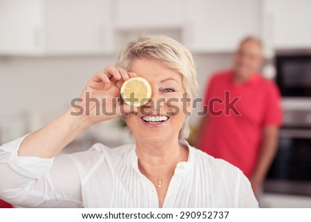 Cheerful Matured Woman Holding Fresh Lemon Slice In Front of her One Eye While Looking at the Camera with a Toothy Smile. - stock photo