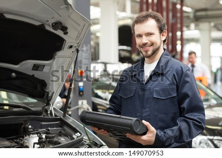 Cheerful mechanic. Young cheerful mechanic standing near the car and smiling - stock photo