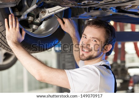 Cheerful mechanic. Young cheerful mechanic working on the car wheel - stock photo