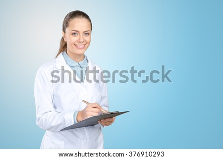 Cheerful medical doctor woman filling out prescription - stock photo