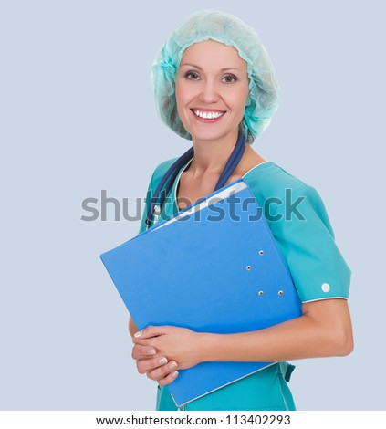 Cheerful medical doctor woman with stethoscope and clipboard. Isolated over grey background - stock photo