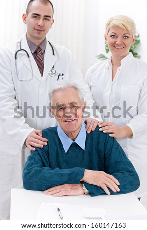 Cheerful medical team with patient in office  - stock photo