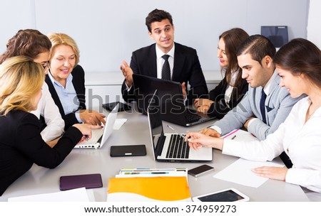 Cheerful members of the multinational business meetings at work in office. Focus on the right man and woman - stock photo
