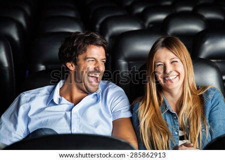 Cheerful mid adult couple laughing while watching film in movie theater - stock photo