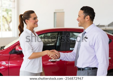cheerful middle aged car dealer handshake with customer in showroom - stock photo