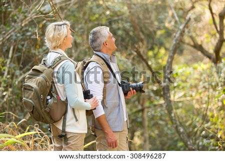 cheerful middle aged couple bird watching in forest  - stock photo