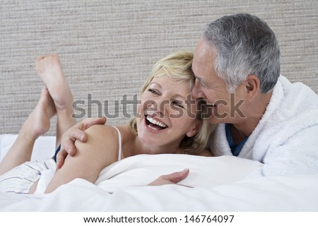 Cheerful middle aged couple lying in bed - stock photo