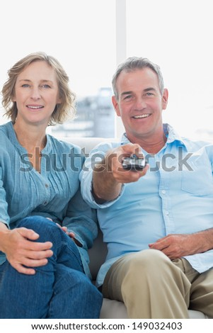 Cheerful middle aged couple sitting on the couch watching tv at home in the living room - stock photo