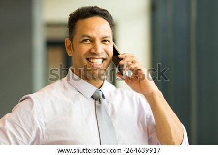 cheerful middle aged employee talking on mobile phone - stock photo