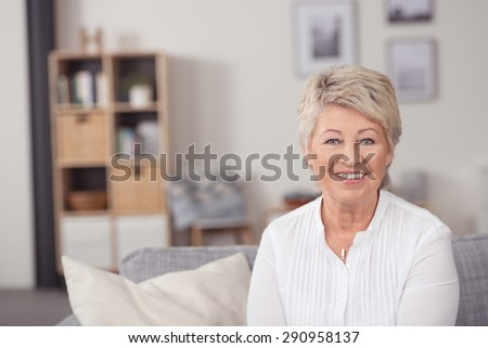 Cheerful Middle Aged Woman with Short Blond Hair, Sitting on the Sofa at the Living Room and Smiling at the Camera. - stock photo
