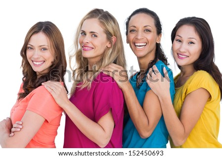 Cheerful models in a line posing with colorful t shirts  on white background - stock photo