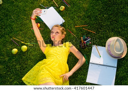 Cheerful modern girl is taking selfie with stationery on the ground. Active young user of social networks. Beautiful young lady adds some new photos to her collection. - stock photo