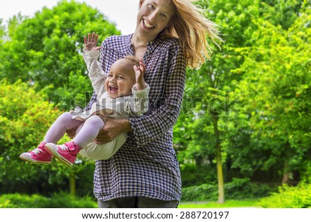 Cheerful mother and daughter on a sunny day - stock photo