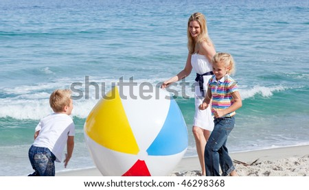 Cheerful mother and her children playing with a ball at the beach - stock photo