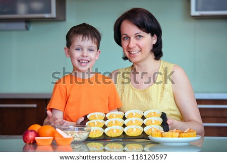 Cheerful mother and her little son presenting their muffins in the kitchen - stock photo