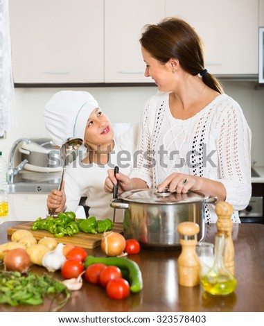 Cheerful mother and her preschooler daughter preparing soup at domestic kitchen. Focus on girl - stock photo