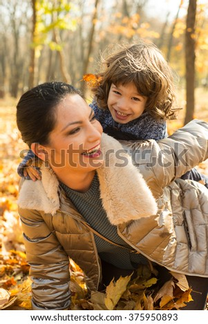 Cheerful mother and her toddler son having fun in autumn park - stock photo