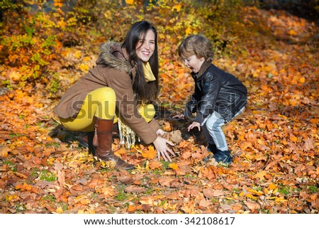 Cheerful mother and son playing with leaves in nature and having fun in autumn. - stock photo