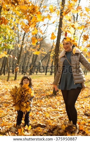 Cheerful mother and son tossing autumn leaves in park and having fun together - stock photo