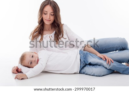Cheerful mother is lying on flooring with her son. She is looking at him with love and caressing his leg. The boy and his mom are gently smiling. Isolated on background - stock photo