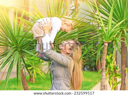 Cheerful mother playing with baby in fresh green palm park, smiling woman lifting up her cute little daughter, happy young family concept  - stock photo