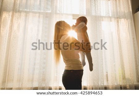 Cheerful mother playing with her baby son against big window in sun rays - stock photo