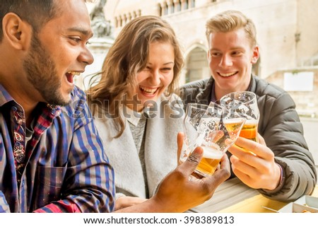 cheerful multi-ethnic friends of drinking beer and say cheers - multi-racial best friends having fun and laughing in a bar - focus on glasses, custom color tones and flare to give spontaneous look - stock photo