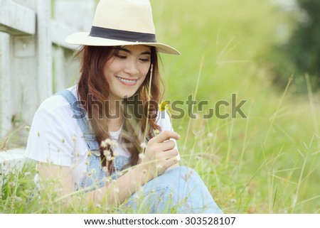Cheerful multiracial Asian woman wearing a hat in the grassland  - stock photo