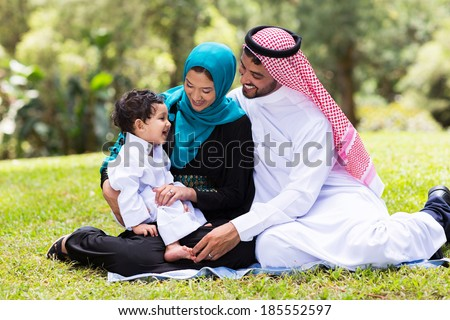 cheerful muslim family sitting outdoors - stock photo