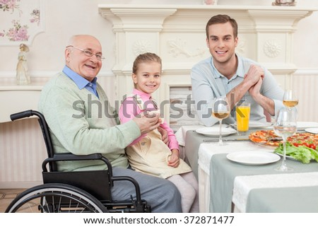 Cheerful old disabled grandfather with his family - stock photo
