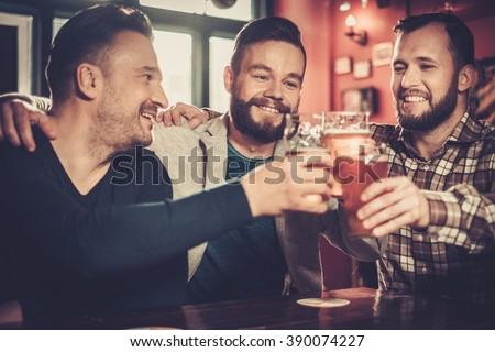 Cheerful old friends having fun and drinking draft beer in pub. - stock photo