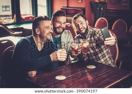 Cheerful old friends having fun taking selfie and drinking draft beer in pub. - stock photo