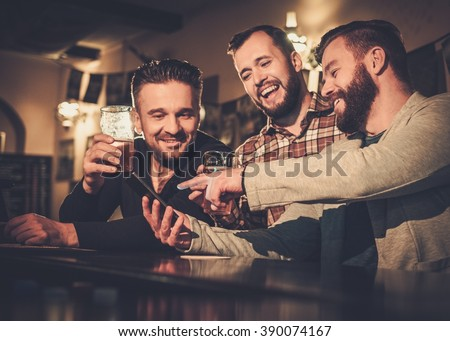 Cheerful old friends having fun with smartphone and drinking draft beer at bar counter in pub. - stock photo