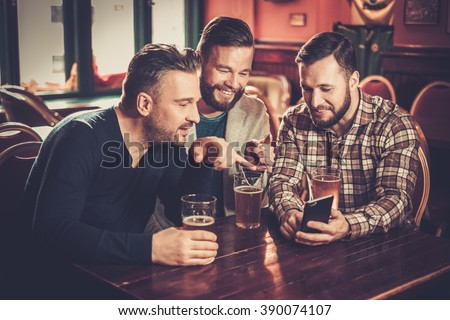 Cheerful old friends having fun with smartphone and drinking draft beer in pub. - stock photo