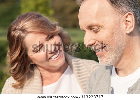 Cheerful old husband and wife are embracing in park. The woman is looking at the man with love. They are standing and smiling - stock photo
