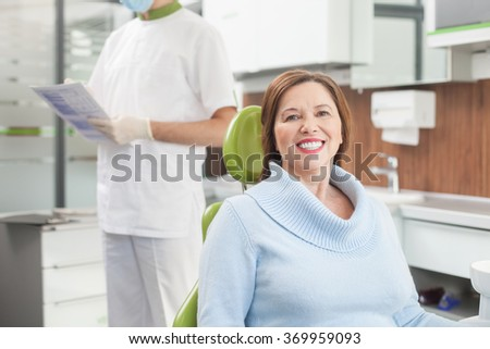 Cheerful old lady is visiting dental doctor - stock photo