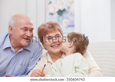 Cheerful old man and woman are caring of their granddaughter. They are sitting on the sofa and smiling. The grandmother is holding a paintbrush. The girl is kissing her with love - stock photo