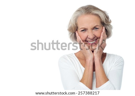 Cheerful old woman with surprised expression - stock photo